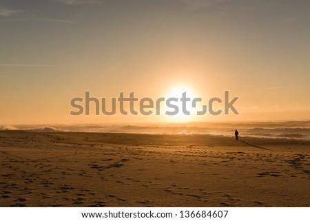 A man walks on an empty beach along the ocean, against a big, golden sunset. - stock photo