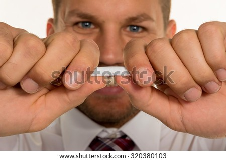 a man wants to quit smoking and breaks his last cigarette - stock photo