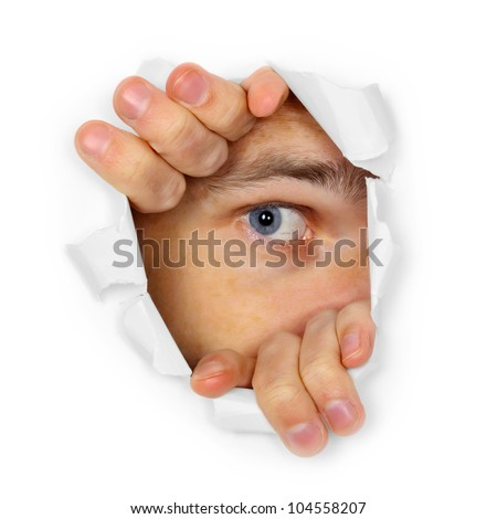 A man watches through a hole in the paper - stock photo
