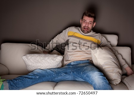 A man watching a scary movie. On the sofa. - stock photo
