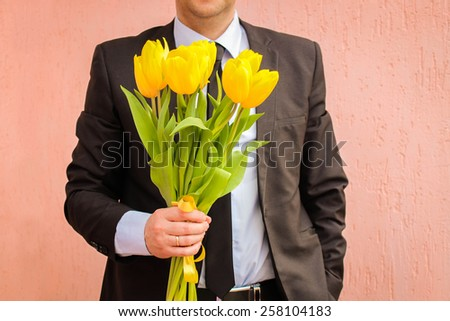A man wearing a business suit, holding a bouquet of yellow tulips. The man gives a bouquet of flowers.  - stock photo