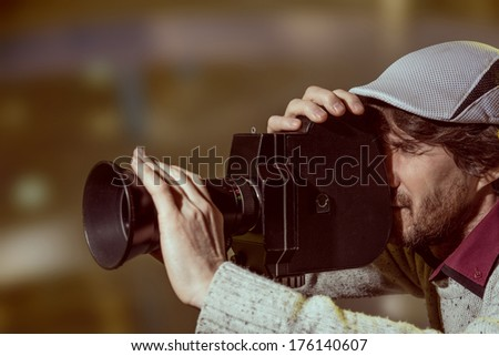 A man wearing a cap with an old movie camera. Shooting reportage - stock photo