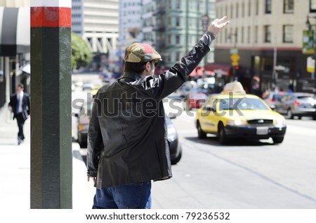 A man wearing a funky cap and black leather jacket at the side of the street hailing a taxi cab - stock photo
