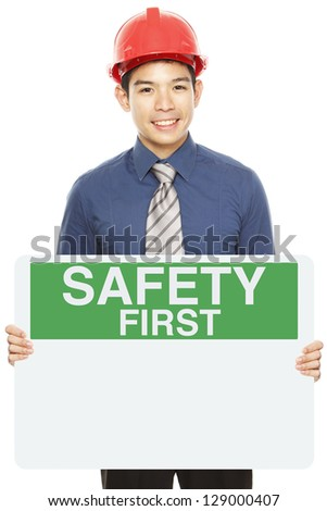 A man wearing a hardhat and holding a blank Safety First sign - stock photo