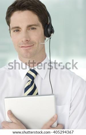 A man wearing a headset holding a folder - stock photo