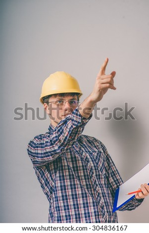a man wearing a helmet directs construction - stock photo