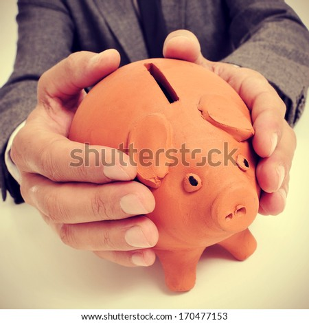 a man wearing a suit sitting in a desk with a piggy bank in his hands - stock photo