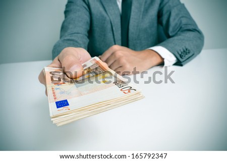 a man wearing a suit sitting in a desk with a wad of euro bills in his hand - stock photo