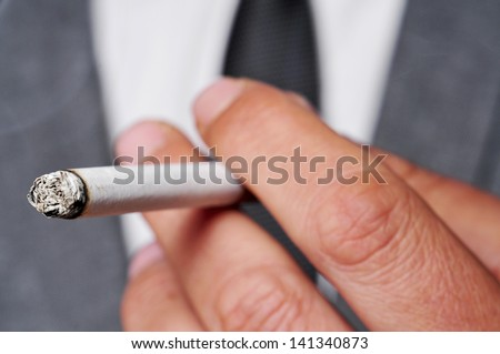 a man wearing a suit smoking a cigarette - stock photo