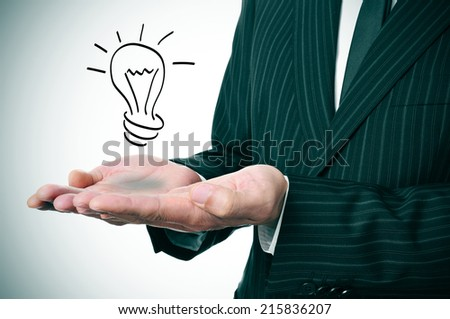 a man wearing a suit with a lightbulb drawn in his hand - stock photo