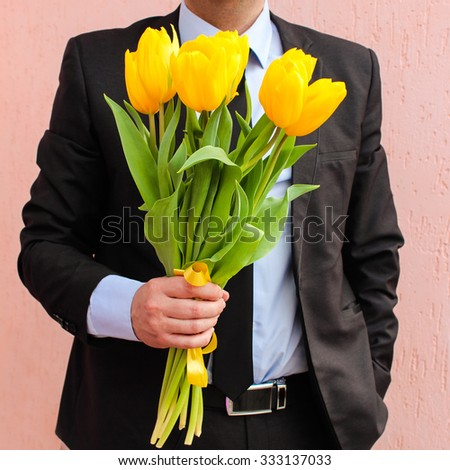 A man wearing business suit, holding bouquet of yellow tulips.  - stock photo