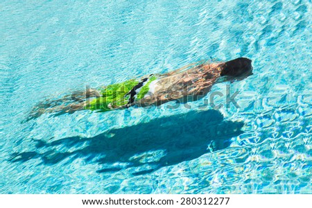 A man wearing green trunks floating under water in a swimming pool. - stock photo