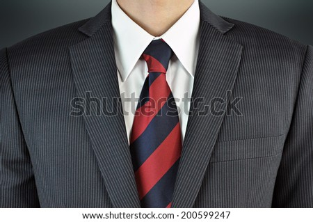 A man wearing suit with stripe necktie - business attire - stock photo