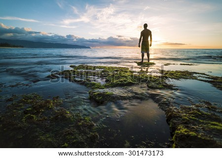 A man wearing surf shorts standing at the edge of a shallow reef looking out into the ocean as the sun sets. Tide pools and green seaweed in the foreground with flowing water.  - stock photo