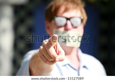 a man wears Hypnotic glasses with a dollar bill taped over his mouth in protest against inflation and the rising cost of goods and services - stock photo