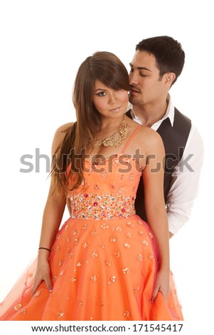 A man whispering into his woman's ear.  She is wearing a formal dress. - stock photo
