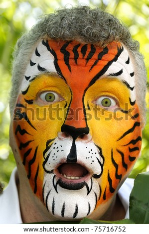 A man who has been painted to look like a tiger, acting surprised. - stock photo