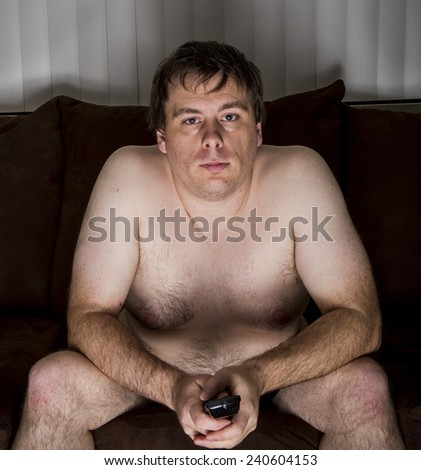 A Man who is naked and overweight watching TV holding a remote - stock photo