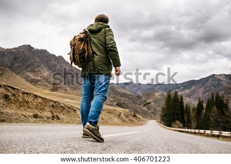 a man with a backpack walks alone on a mountain road - stock photo