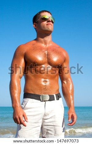 A man with a beautiful muscular body relaxing on the beach - stock photo