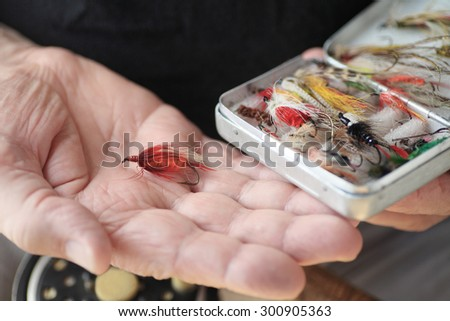 A man with a box of fly fishing flies, one in his hand - stock photo