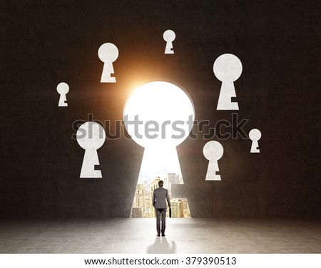 A man with a case standing in front of a huge keyhole, many keyholes around it, city and sky seen through it. Black background. Back view. Concept of finding the way - stock photo