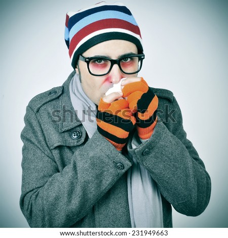 a man with a cold bundled up in a coat, knit cap, gloves and scarf - stock photo