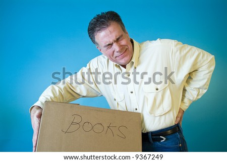 A man with a grimace on his face holding his back as if injured due to lifting a box of books. - stock photo