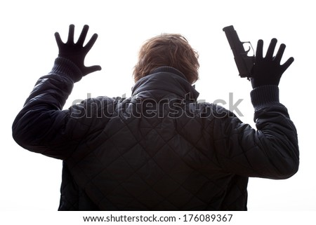 A man with a gun holding his hands up - stock photo