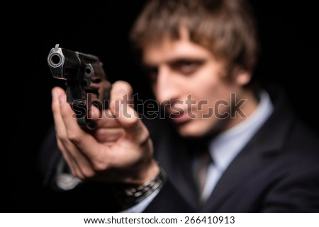 a man with a gun in studio. weapons, crime.  photo a young man drawing a gun in self defense studio shoot - stock photo