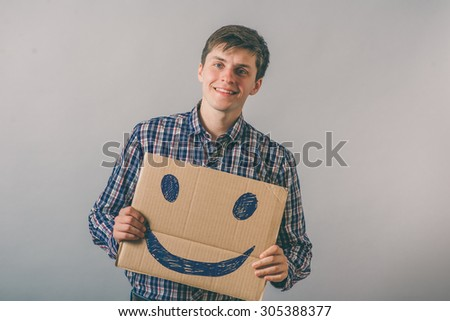 a man with a happy smiley on cardboard - stock photo