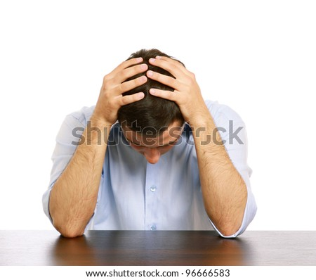 A man with a headache at the desk, isolated on white background - stock photo
