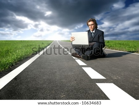 a man with a laptop on the street - stock photo