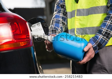 A man with a reflective vest is fueling a vehicle with a plastic canister. - stock photo