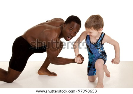 A man with a shocked expression on his face as the young boy is winning the arm wrestling. - stock photo