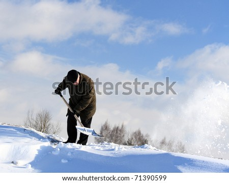 A man with a shovel removing snow from a driveway - stock photo