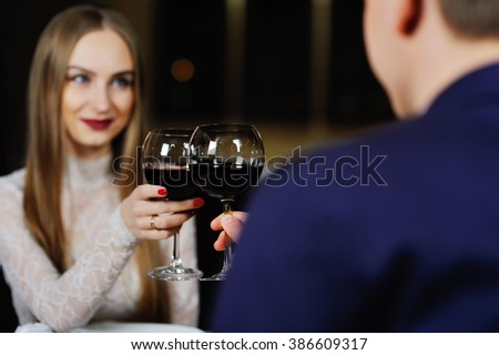 a man with a woman drinking red wine in a restaurant - stock photo