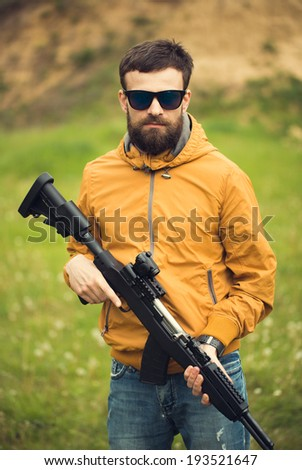 A man with an automatic rifle outdoor - stock photo