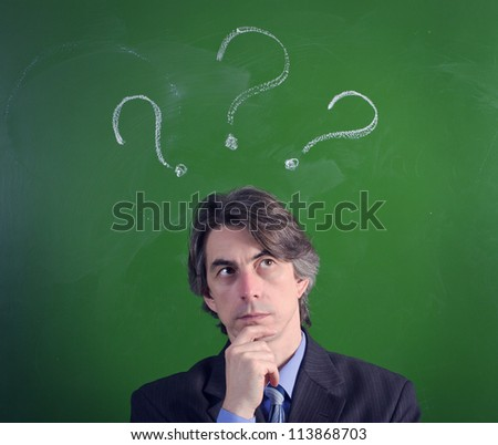 A man with an expression of questioning and question marks over their heads - stock photo