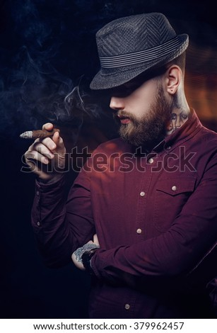 A man with beard in a hat smoking a cigar. - stock photo