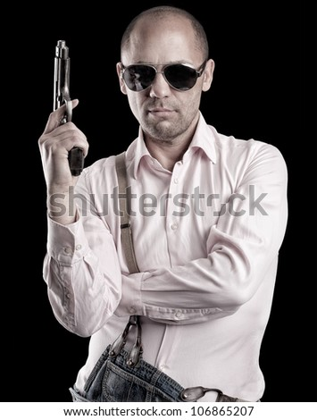 A man with glasses holding a gun. - stock photo