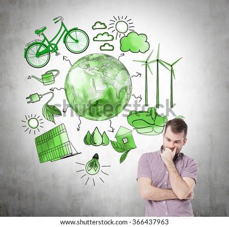 A man with hand on his chin thinking about energy, symbols of alternative energy sources painted in green colours on a concrete wall. Green Earth in the middle. Concept of clean environment - stock photo