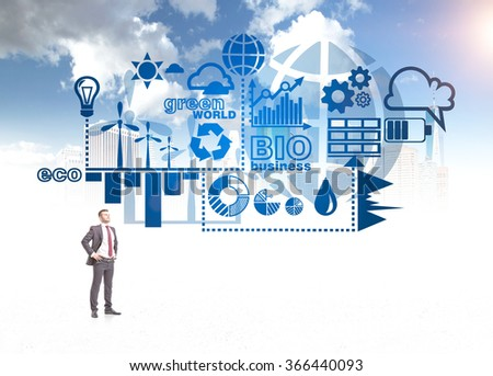 A man with hands on hips looking up and imagining symbols of alternative energy sources. Blue sky at the background. Concept of clean environment. - stock photo