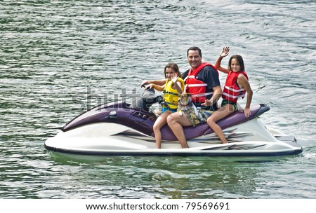 A man with his girls and dog waving from a jet ski. - stock photo