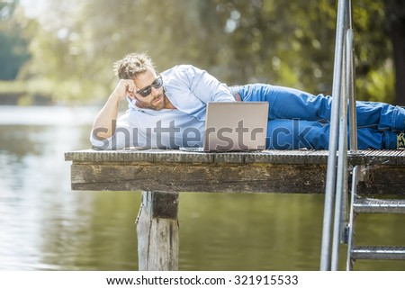 A man with his notebook is working outdoor at the lake - stock photo