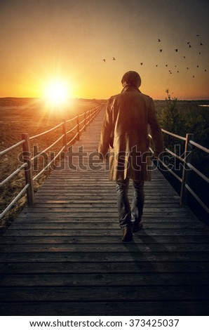 A man with long coat walking in a boardwalk into de sunset - stock photo