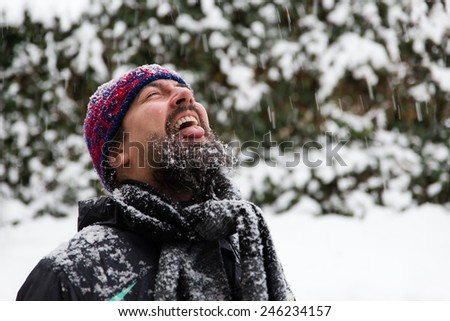 a man with outstretched tongue is catching snowflakes - stock photo