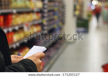 A man with shopping list, grocery store shelves and products in background - stock photo