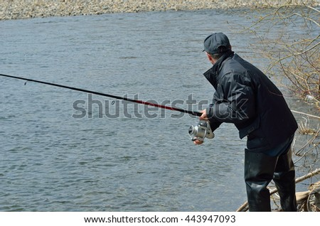 A man with spinning rod on fishing. - stock photo