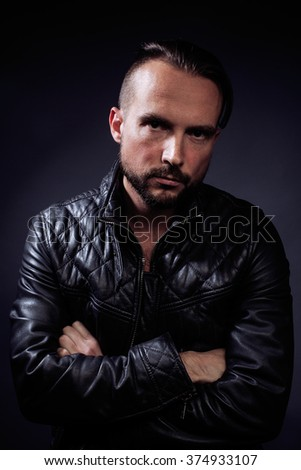 A man with tattooes on his arms. Silhouette of muscular body. caucasian brutal hipster guy with modern haircut, looking like criminal - stock photo
